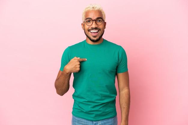 Homem jovem e bonito colombiano isolado em um fundo rosa com expressão facial surpresa