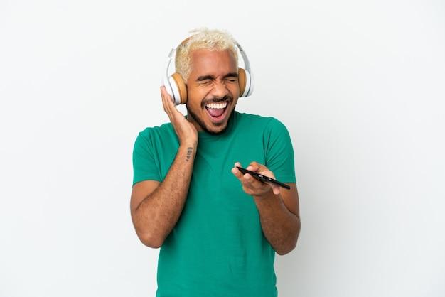 Homem jovem e bonito colombiano isolado no fundo branco, ouvindo música com um celular e cantando