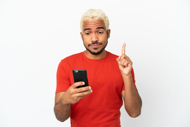 Homem jovem e bonito colombiano isolado no fundo branco, usando telefone celular e levantando o dedo