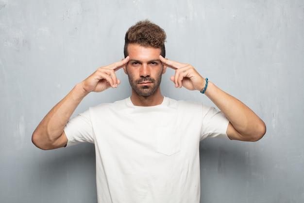 Homem jovem e bonito com um olhar confuso e pensativo, olhando de soslaio