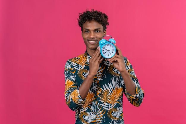 Homem jovem e bonito de pele escura sorridente com cabelo encaracolado em uma camisa estampada de folhas segurando um despertador azul e mostrando as horas em um fundo rosa