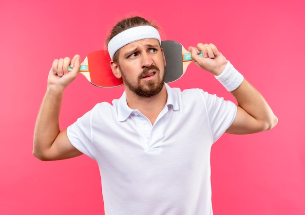 Homem jovem e bonito, desagradável e esportivo, usando bandana e pulseiras, segurando raquetes de pingue-pongue atrás da cabeça e olhando para o lado isolado no espaço rosa