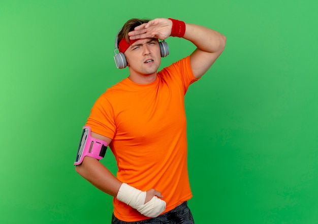 Homem jovem e bonito, desagradável e esportivo usando fita para a cabeça e pulseiras e fones de ouvido e uma braçadeira de telefone com o pulso enrolado com bandagem colocando a mão na testa olhando direto