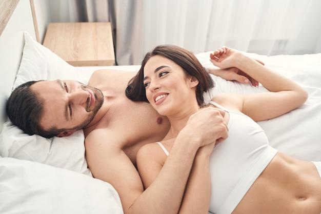 Homem jovem e bonito e sereno, caucasiano, relaxando na cama com sua esposa de cabelos escuros.