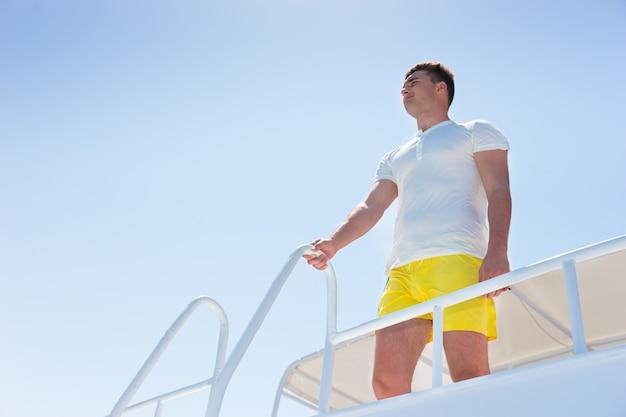 Homem jovem e bonito em pé no iate, segurando a grade em um dia ensolarado de verão
