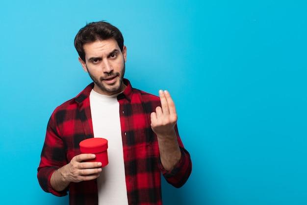 Homem jovem e bonito fazendo capice ou gesto de dinheiro, dizendo para você pagar suas dívidas!