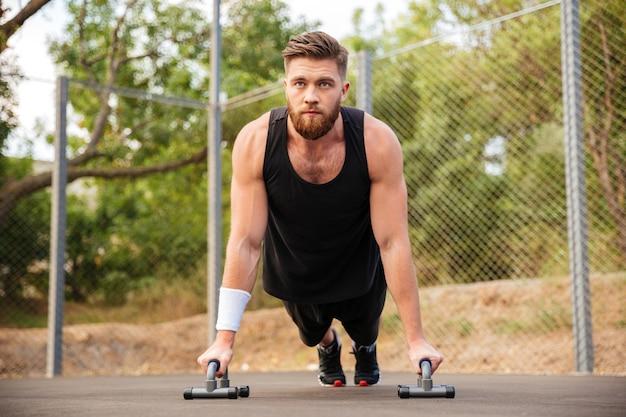 Homem jovem e bonito fitness fazendo exercícios de flexão com equipamento esportivo ao ar livre