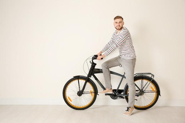 Homem jovem e bonito hippie com bicicleta perto da parede de luz