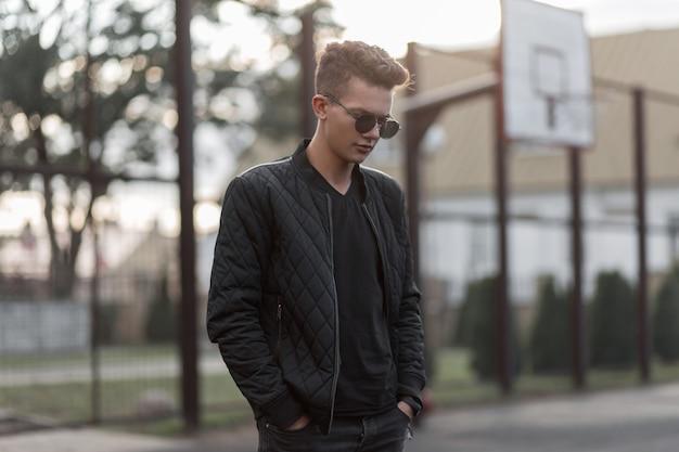 Homem jovem e bonito hippie com óculos de sol elegantes numa jaqueta preta da moda fica em um estádio na rua