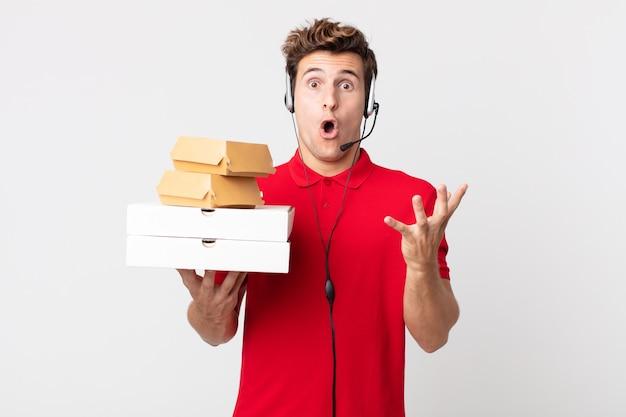 Homem jovem e bonito maravilhado, chocado e atônito com uma surpresa inacreditável. conceito de comida rápida para viagem