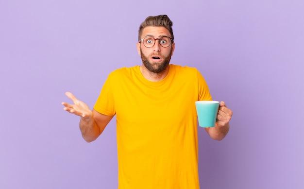 Homem jovem e bonito maravilhado, chocado e atônito com uma surpresa inacreditável. e segurando uma caneca de café