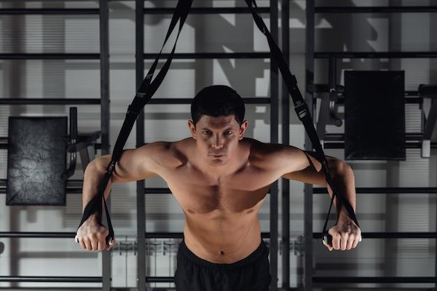 Homem jovem e bonito musculoso treinando com trx enquanto trabalhava no ginásio.