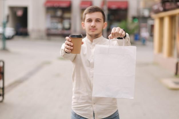 Homem jovem e bonito na cidade segurando um pacote e uma xícara de café