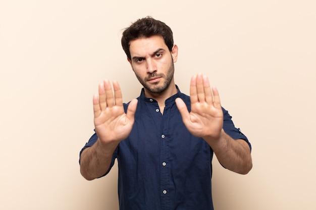 Homem jovem e bonito parecendo sério, infeliz, zangado e descontente, proibindo a entrada ou dizendo para pare com as palmas das mãos abertas