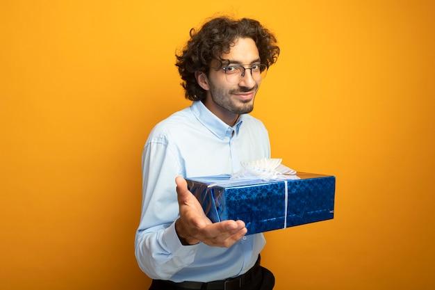 Homem jovem e bonito satisfeito, usando óculos, segurando um pacote de presente, olhando para a frente, isolado na parede laranja
