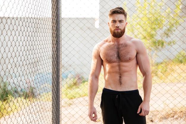 Homem jovem e bonito sem camisa de fitness durante treino ao ar livre