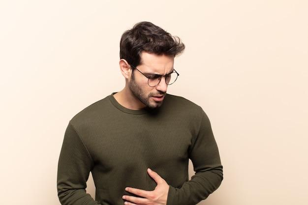 Homem jovem e bonito sentindo-se ansioso, doente, doente e infeliz, com uma forte dor de estômago ou gripe