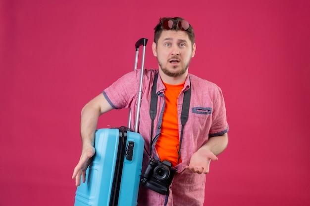 Homem jovem e bonito viajante com uma câmera parada com uma mala parecendo confuso encolhendo os ombros parecendo incerto e confuso