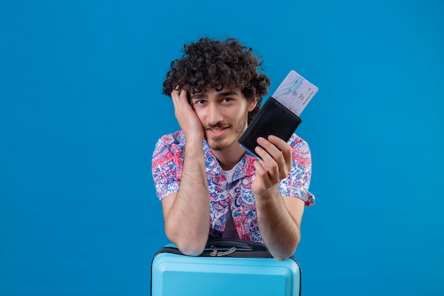Homem jovem e bonito viajante encaracolado satisfeito segurando as passagens de avião, a carteira colocando a mão na bochecha e o braço na mala em um espaço azul isolado com espaço de cópia