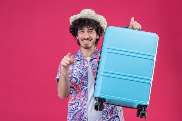 Homem jovem e bonito viajante encaracolado sorridente com chapéu e mala levantada apontando na parede rosa isolada com espaço de cópia