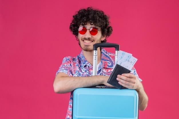 Homem jovem e bonito viajante encaracolado sorridente, usando óculos escuros, segurando uma carteira e bilhetes de avião, olhando para o lado esquerdo com as mãos na mala na parede rosa isolada com espaço de cópia