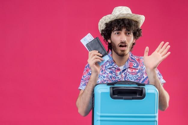 Homem jovem e bonito viajante encaracolado surpreso, usando um chapéu segurando passagens de avião e carteira com mala na parede rosa isolada com espaço de cópia