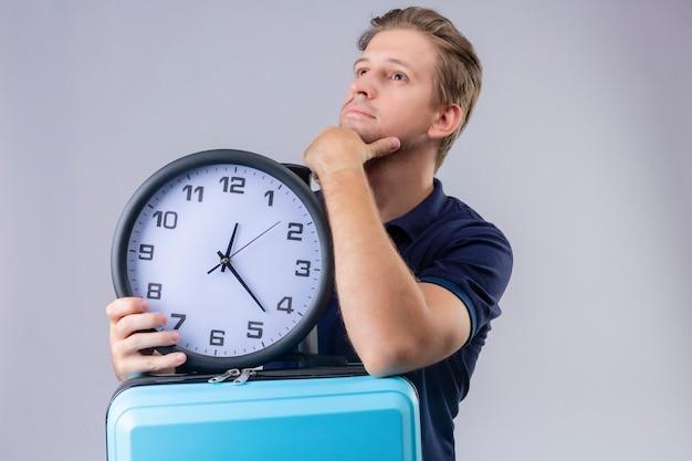 Homem jovem e bonito viajante segurando o relógio com a mão no queixo, olhando para longe com expressão pensativa, pensando sobre o fundo branco