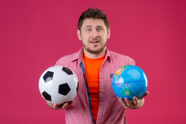 Homem jovem e bonito viajante segurando uma bola de futebol e um globo com uma expressão confusa