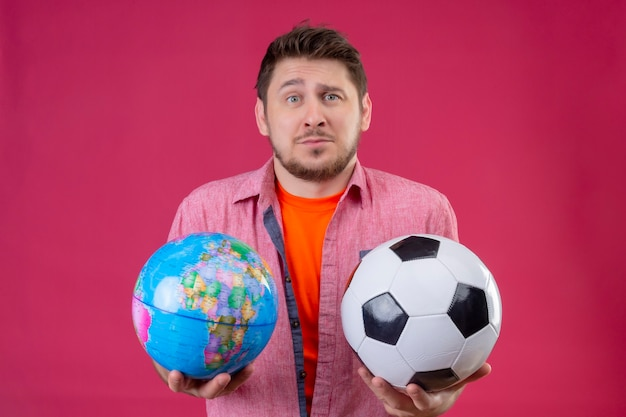 Homem jovem e bonito viajante segurando uma bola de futebol e um globo, parecendo confuso e incerto