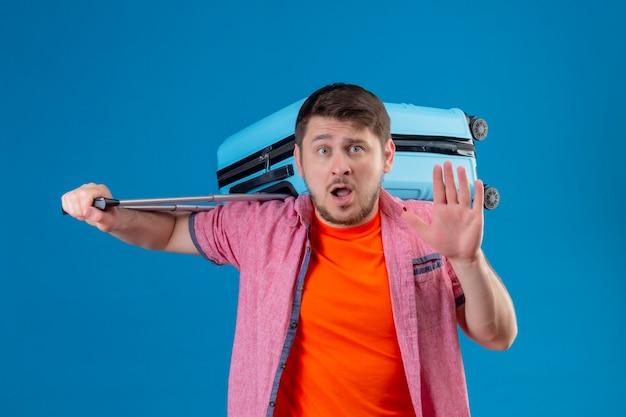 Homem jovem e bonito viajante segurando uma mala fazendo um sinal de pare com a mão assustada em pé sobre a parede azul