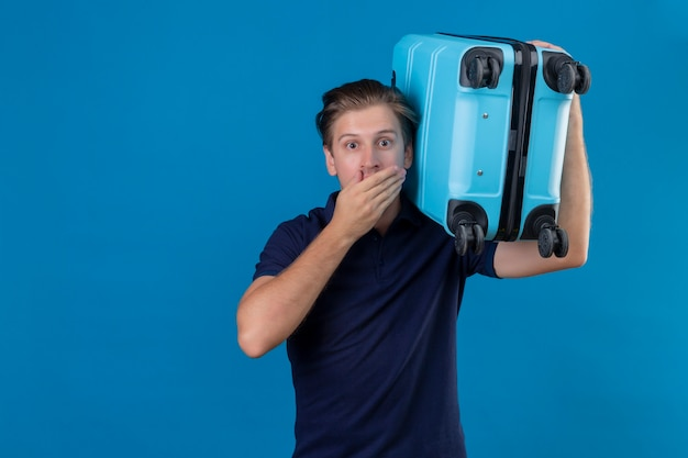 Homem jovem e bonito viajante segurando uma mala parecendo espantado e surpreso, cobrindo a boca com a mão em pé sobre um fundo azul