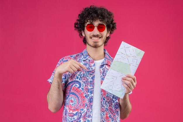 Homem jovem e bonito viajante sorridente usando óculos escuros segurando um mapa e apontando para ele na parede rosa isolada com espaço de cópia