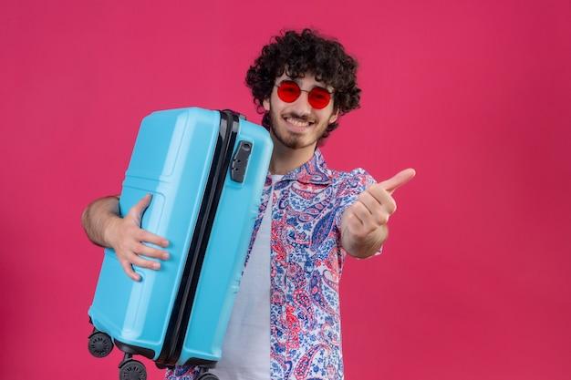 Homem jovem e bonito viajante sorridente usando óculos escuros, segurando uma mala e apontando para o lado direito em uma parede rosa isolada com espaço de cópia