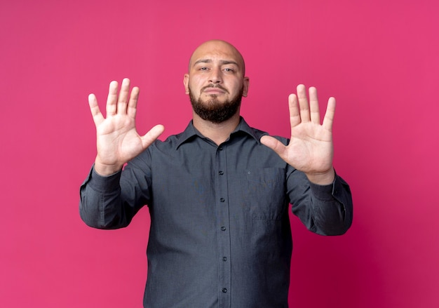 Homem jovem e careca de call center esticando as mãos na frente gesticulando para parar isolado na parede carmesim