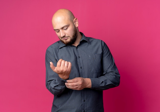 Homem jovem e careca de call center olhando e agarrando a manga de sua camisa, isolada em um fundo carmesim com espaço de cópia