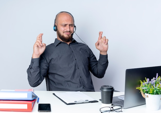 Homem jovem e careca descontente de call center usando fone de ouvido, sentado à mesa com ferramentas de trabalho, olhando para um laptop com dedos cruzados isolados no fundo branco