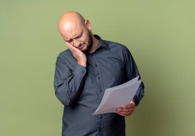 Homem jovem e careca dolorido de call center segurando documentos e colocando a mão na bochecha sofrendo de dor de dente isolada em verde oliva com espaço de cópia