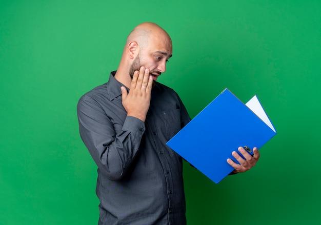 Homem jovem e careca impressionado do call center segurando e olhando para uma pasta aberta e tocando o rosto isolado no verde com espaço de cópia