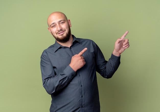Homem jovem e careca satisfeito do call center apontando para o lado isolado em um fundo verde oliva com espaço de cópia