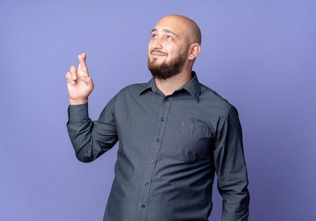 Homem jovem e careca satisfeito do call center olhando para cima fazendo gesto de dedos cruzados isolado no fundo roxo