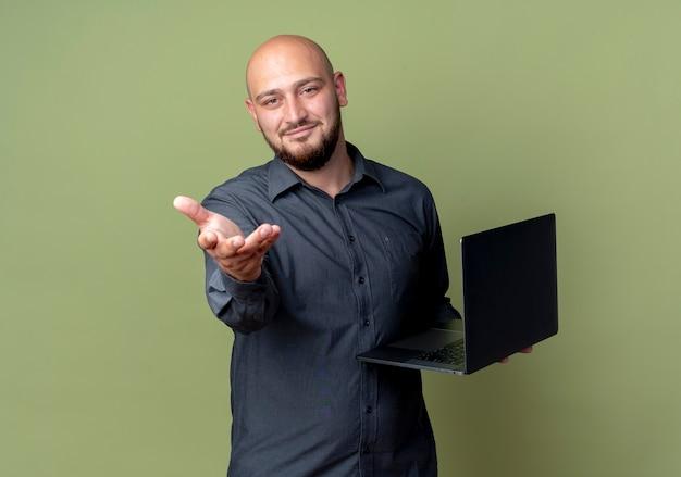 Homem jovem e careca satisfeito segurando um laptop e estendendo a mão para a câmera, isolado em um fundo verde oliva com espaço de cópia