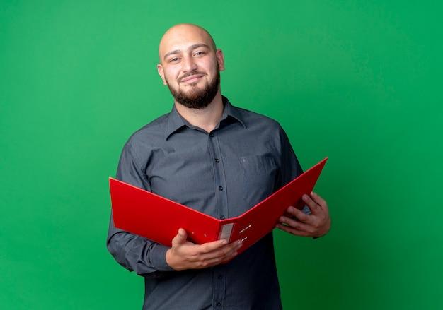Homem jovem e careca satisfeito segurando uma pasta aberta, isolada em um fundo verde com espaço de cópia