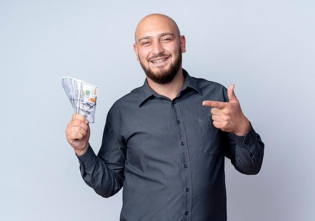 Homem jovem e careca sorridente de call center segurando e apontando para o dinheiro isolado na parede branca