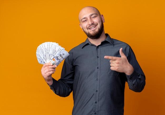Homem jovem e careca sorridente de call center segurando e apontando para o dinheiro isolado na parede laranja
