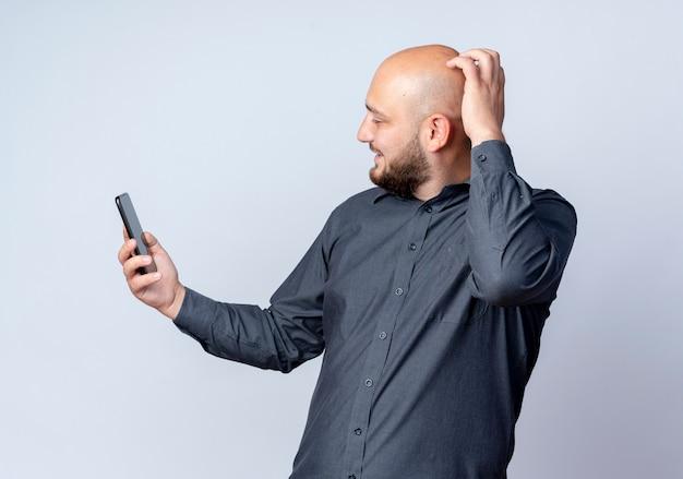 Homem jovem e careca sorridente de call center segurando e olhando para o celular com a mão na cabeça isolada na parede branca