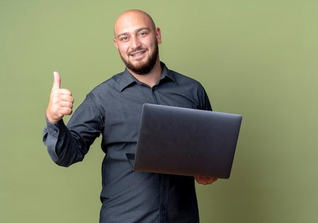 Homem jovem e careca sorridente de call center segurando um laptop e mostrando o polegar isolado na parede verde oliva