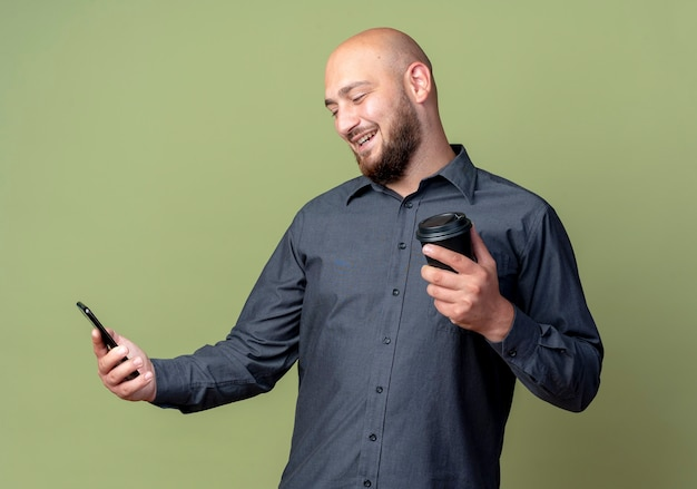 Homem jovem e careca sorridente, segurando e olhando para o telefone celular com uma xícara de café de plástico na outra mão, isolada na parede verde oliva