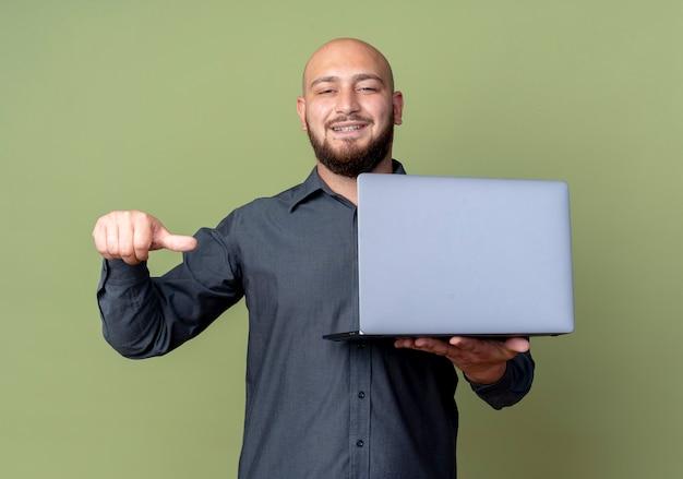 Homem jovem e careca sorridente, segurando um laptop e apontando para ele, isolado na parede verde oliva