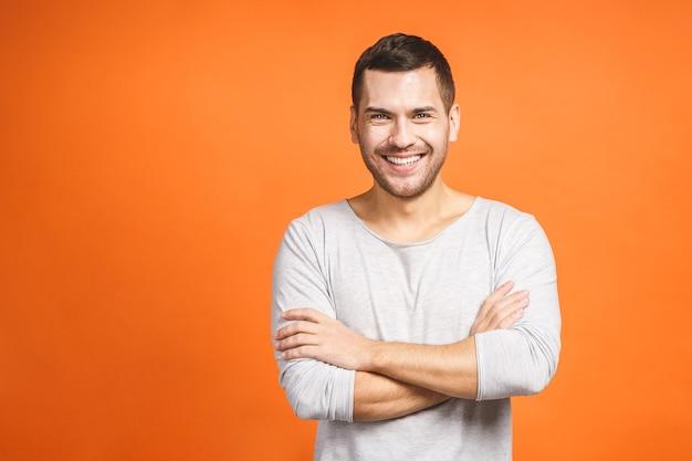 Homem jovem e confiante, bonito, de braços cruzados e sorrindo, em pé contra um fundo laranja
