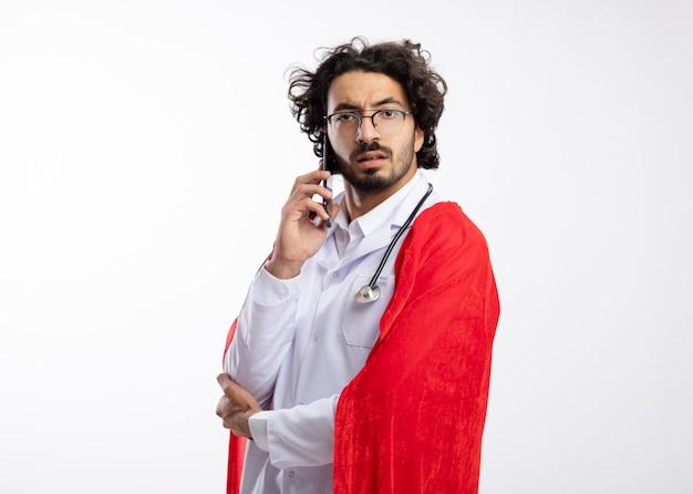 Homem jovem e confiante super-herói caucasiano com óculos ópticos, uniforme de médico com capa vermelha e estetoscópio no pescoço fica de lado, falando ao telefone